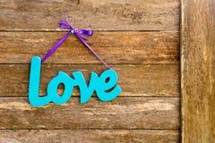 Amour - mot en bois peint par turquoise bleue sur le hangi pourpre de ruban Photo libre de droits