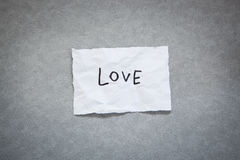 Amour - mot sur le livre blanc avec le fond gris Photos stock