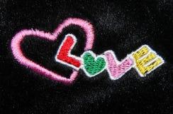 Amour multicolore de mot de broderie de main sur la fourrure noire Photo libre de droits