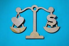 Amour ou argent sur des échelles, photos stock