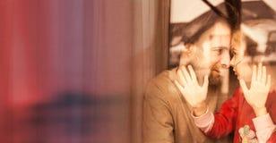 Amour - père et fille étreignant par la fenêtre Image libre de droits