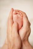 Amour - pieds nouveau-nés dans des mains du père Images libres de droits