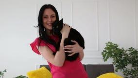 Amour pour des animaux familiers belle danse aux cheveux foncés de fille avec un chat noir à la maison dans le salon banque de vidéos