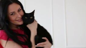 Amour pour des animaux familiers belle danse aux cheveux foncés de fille avec un chat noir à la maison dans le salon clips vidéos