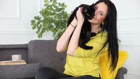Amour pour des animaux familiers la belle fille aux cheveux foncés avec un chat noir détend à la maison dans le salon sur le diva clips vidéos