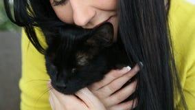 Amour pour des animaux familiers la belle fille aux cheveux foncés avec un chat noir détend à la maison dans le salon sur le diva banque de vidéos