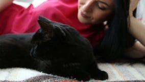 Amour pour des animaux familiers la belle fille aux cheveux foncés avec un chat noir détend à la maison dans la salle de lit clips vidéos