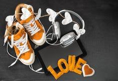 Amour pour le concept de musique Espadrilles, écouteurs, comprimé et h oranges Images libres de droits
