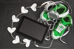 Amour pour le concept de musique Espadrilles, écouteurs, comprimé et h verts Images stock