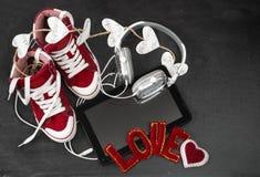 Amour pour le concept de musique Espadrilles, écouteurs, comprimé et hea rouges Photo libre de droits
