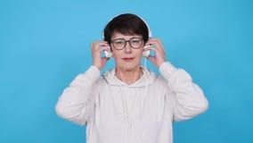Amour pour le concept de musique La femme mûre coule la musique dans des écouteurs sur un fond bleu banque de vidéos