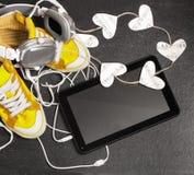 Amour pour le concept de musique Les espadrilles jaunes, écouteurs, comprimé, entendent Photographie stock libre de droits
