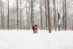 Amour, relations, saison, amitié et concept de personnes - homme et femme marchant dans la forêt d'hiver Photo stock