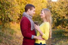 Amour, relations, saison, amitié et concept de personnes - homme heureux et femme appréciant l'automne d'or d'automne avec le cof Photos libres de droits