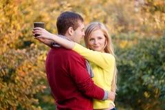 Amour, relations, saison, amitié et concept de personnes - homme heureux et femme appréciant l'automne d'or d'automne avec le cof Image stock