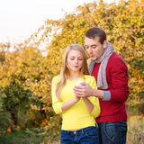 Amour, relations, saison, amitié et concept de personnes - homme heureux et femme appréciant l'automne d'or d'automne avec le cof Images libres de droits