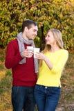 Amour, relations, saison, amitié et concept de personnes - homme heureux et femme appréciant l'automne d'or d'automne avec le cof Images stock