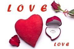 Amour Roses rouges, une bague de fiançailles et coeur Photographie stock