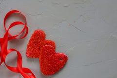 Amour rouge de coeur entre deux personnes sur un fond gris Concept de jour du ` s de Valentine Photographie stock