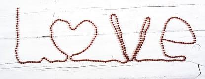 Amour rouge de mot de ruban d'isolement sur le fond en bois blanc Image libre de droits