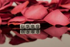 Amour sur des perles avec des pétales de rose Photos libres de droits
