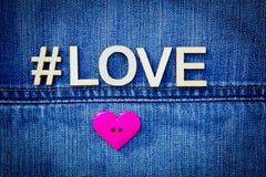 Amour sur le denim avec le bouton rose de coeur Photos stock
