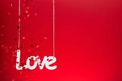 Amour sur le fond rouge avec des confettis Photo stock