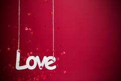 Amour sur le fond rouge avec des confettis Photographie stock