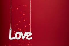 Amour sur le fond rouge avec des confettis Images stock