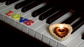 Amour sur les clés de piano et la lumière de bougie banque de vidéos