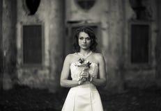 Amour sur les pierres froides - la jeune mariée se tient avec un bouquet de mariage dedans Photos libres de droits