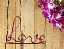 Amour tordu de mot de ruban avec des orchidées sur le bois Images libres de droits
