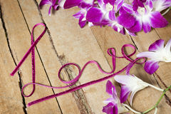 Amour tordu de mot de ruban sur le bois avec des orchidées Photo libre de droits