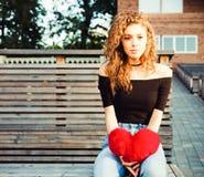 Amour, tristesse et solitude Belle fille aux cheveux longs dans la soirée triste d'été de solitude Elle tient un grand rouge Photo libre de droits