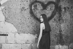 Amour unilatéral Femme posant avec le graffiti de coeur sur le mur gris Image stock