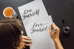 Amour vous-m?me Le calligraphe Young Woman ?crit l'expression sur le livre blanc Inscrire les lettres d?cor?es ornementales photographie stock