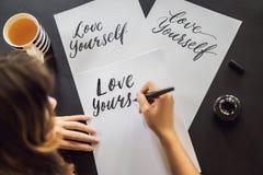 Amour vous-m?me Le calligraphe Young Woman ?crit l'expression sur le livre blanc Inscrire les lettres d?cor?es ornementales photographie stock libre de droits