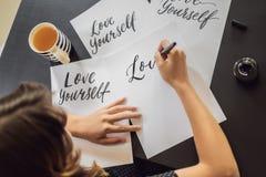 Amour vous-m?me Le calligraphe Young Woman ?crit l'expression sur le livre blanc Inscrire les lettres d?cor?es ornementales photos libres de droits