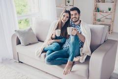 Amour vrai Le couple romantique gai se repose sur le sofa sous le coz Images stock