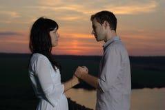 Amoureux au coucher du soleil et au lac Photographie stock