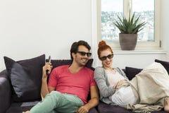 Amoureux avec les verres 3d se reposant sur le sofa Image libre de droits