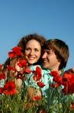Amoureux dans un domaine avec des pavots Photos libres de droits