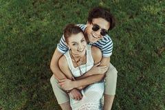 Amoureux de sourire étreignant et regardant l'appareil-photo tout en se reposant sur l'herbe Photographie stock
