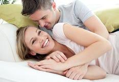 Amoureux joyeux ayant l'amusement ensemble sur un sofa image stock