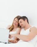 Amoureux observant un film sur leur ordinateur portatif Photographie stock libre de droits