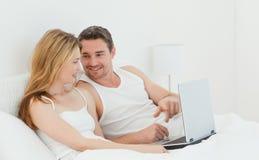 Amoureux observant un film sur leur ordinateur portatif Photos stock