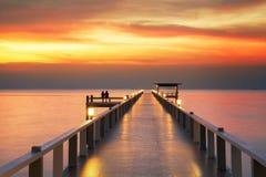 Amoureux sur le pont boisé avec le coucher du soleil Images stock