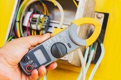 Amp σφιγκτηρών μετρητής, χέρι του ηλεκτρολόγου με amp σφιγκτηρών το μετρητή Στοκ Φωτογραφία