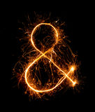 Ampersand symbol made of firework sparklers at night royalty free stock images