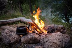 Сampfire. And the old kettle in twilight Stock Photography